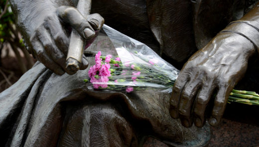 Flowers lie at the Art Rooney statue outside Heinz Field. (Lake Fong/Post-Gazette)