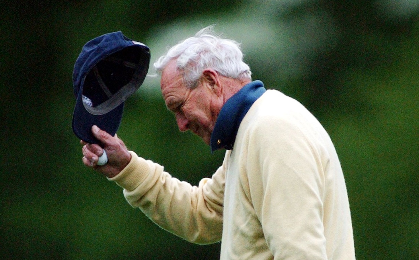 Arnold Palmer tips his hat to the gallery as he walks on the 12th hole during first round play of the 2003 Masters. (David Martin/Associated Press)