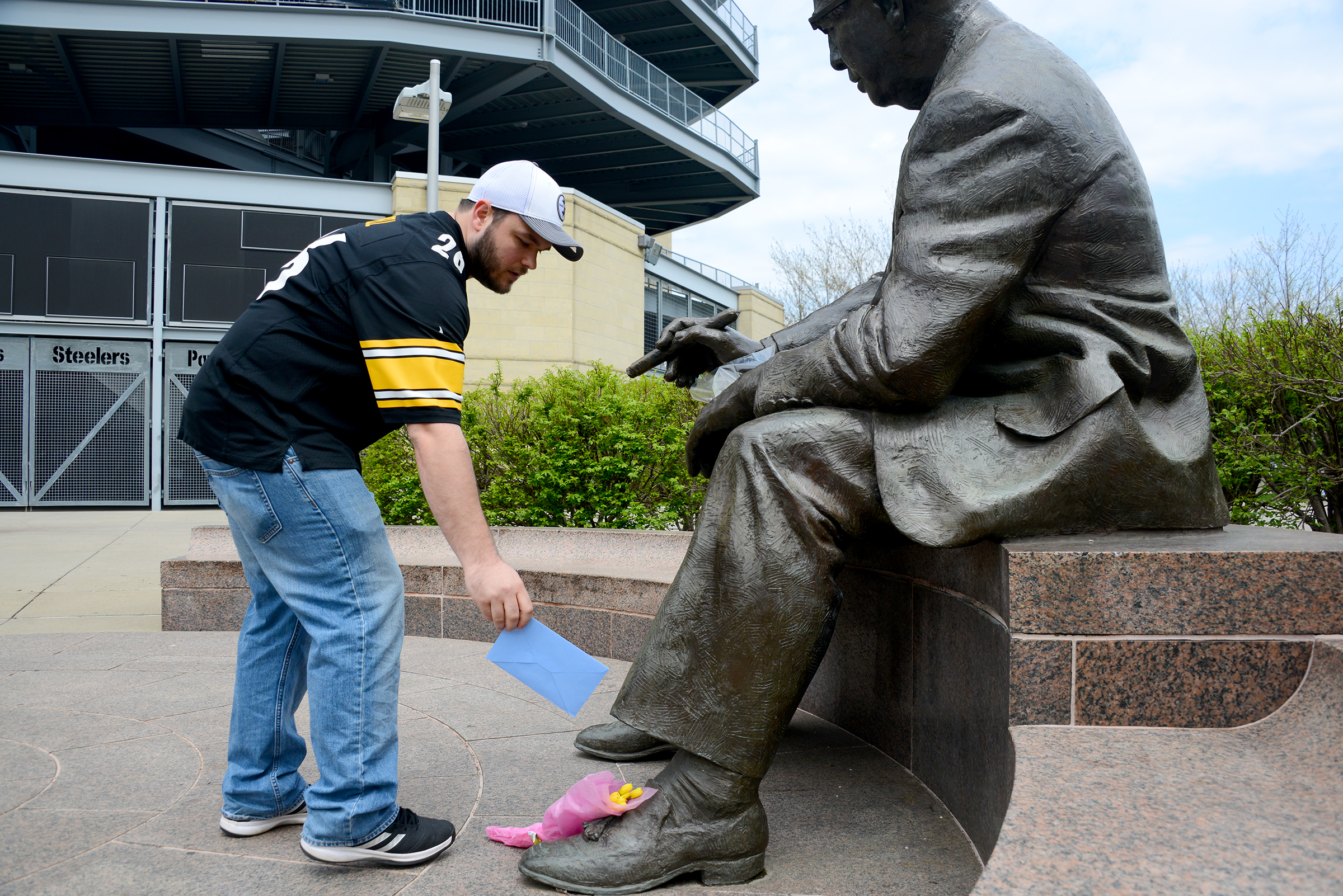 Robert Turner, 31, of Fox Chapel places a card at the Art Rooney statue outside Heinz Field. (Lake Fong/Post-Gazette)