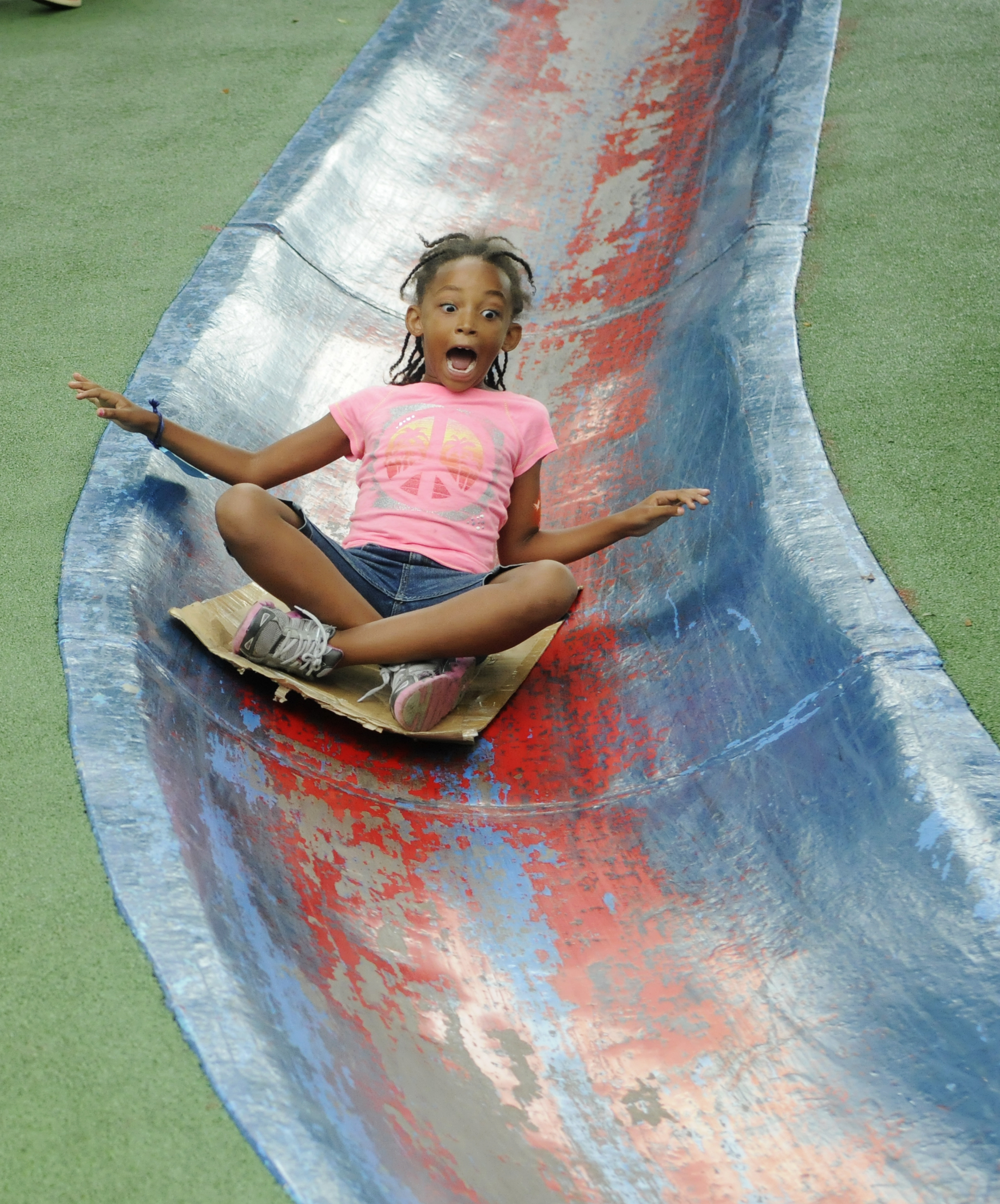 Ailani Mitchell of Homewood, goes down the blue slide at Blue Slide Playground in Frick Park. (Chris Kasprak/Post-Gazette)