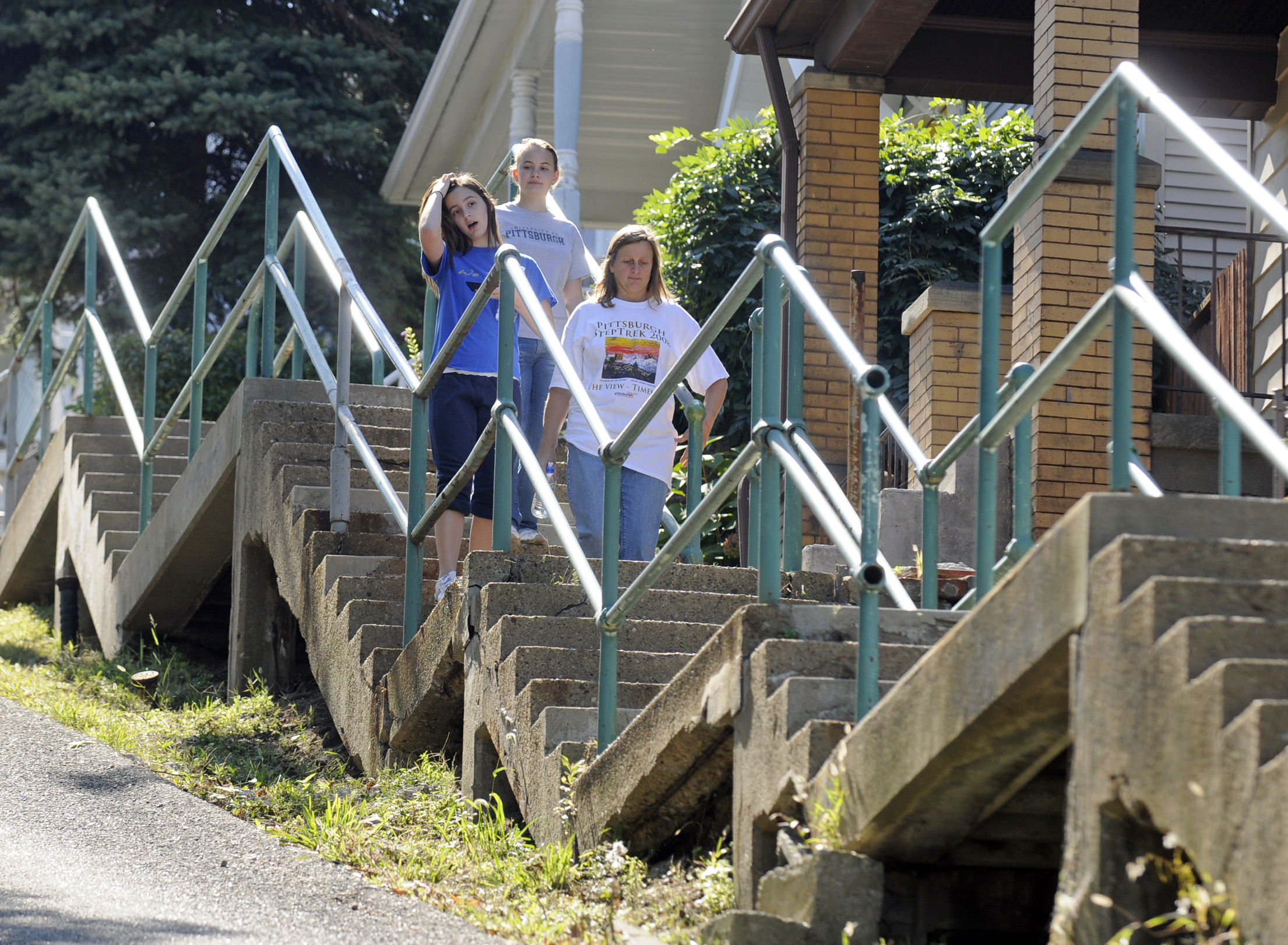 In somewhat of a busman's holiday, Patty Landon (right) leads her daughters Christine (left), 16, and Kate, 20, down the long series of steps along Sterling St. on Pittsburgh's South Side Slopes during the 8th annual Step Trek. (Bob Donaldson/Post-Gazette)